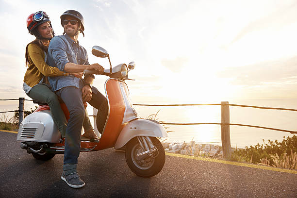A shot of a young couple riding on a scooter